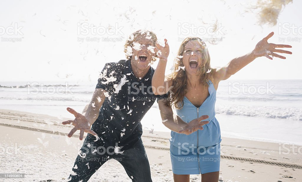 Excited couple after a pillow fight on the beach royalty-free stock photo