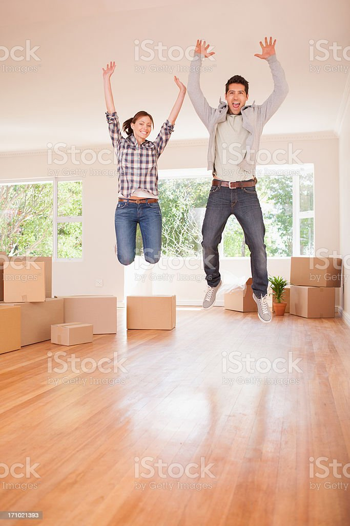 Excited couple jumping in new house stock photo
