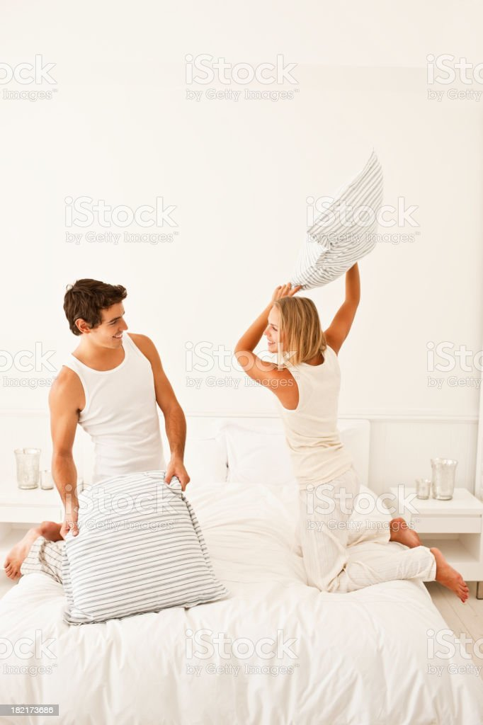 Excited couple pillow fighting at home stock photo
