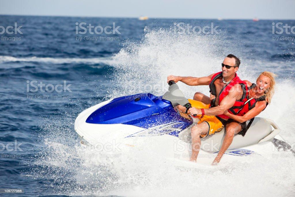Excited couple riding jetski stock photo