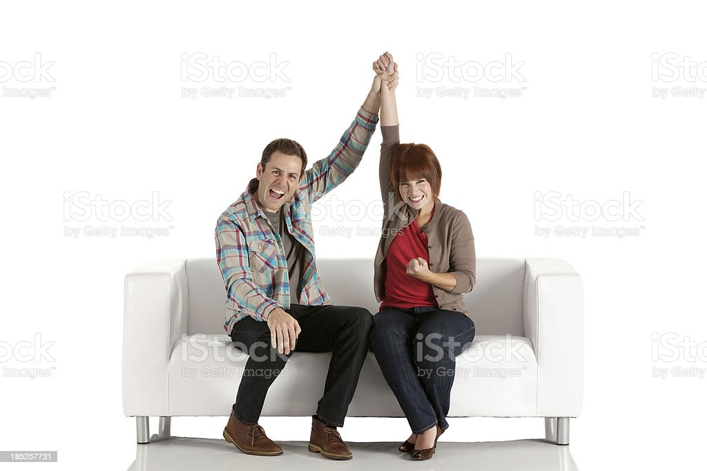Excited couple sitting on a couch royalty-free stock photo