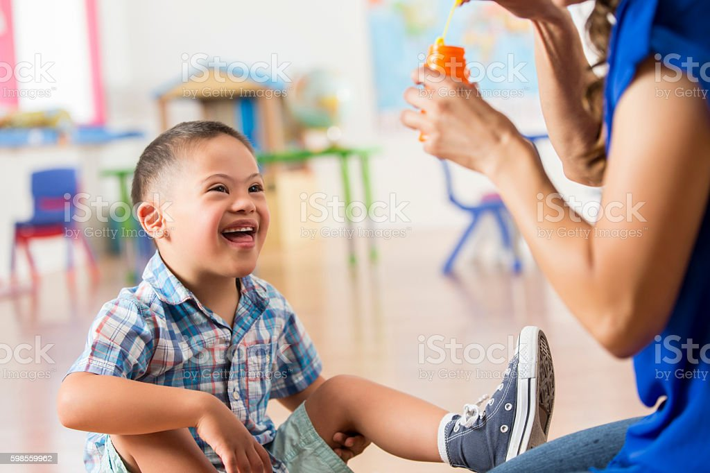 Excited Down Syndrome boy playing with bubbles at daycare stock photo