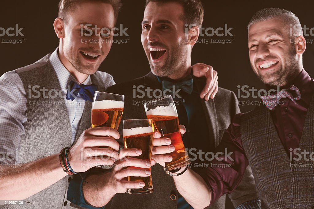 Excited elegant businessmen toasting with beer in nightclub stock photo