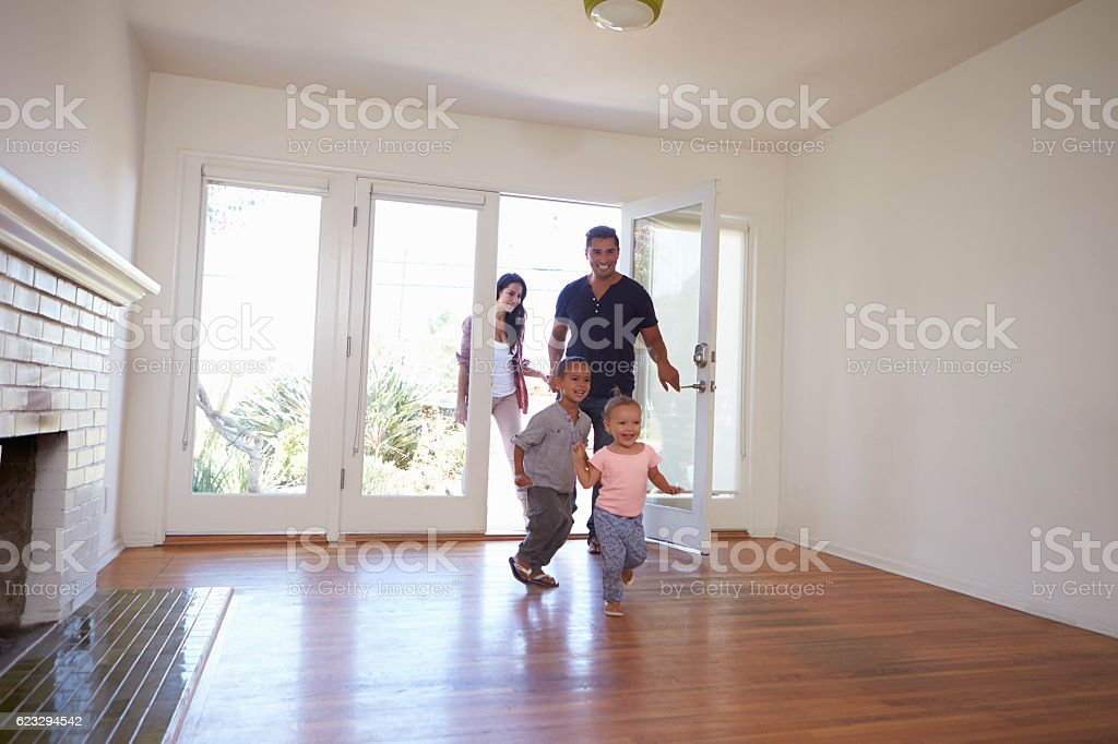 Excited Family Explore New Home On Moving Day stock photo