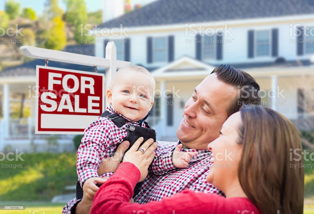 Excited Family In Front of For Sale Sign and House stock photo