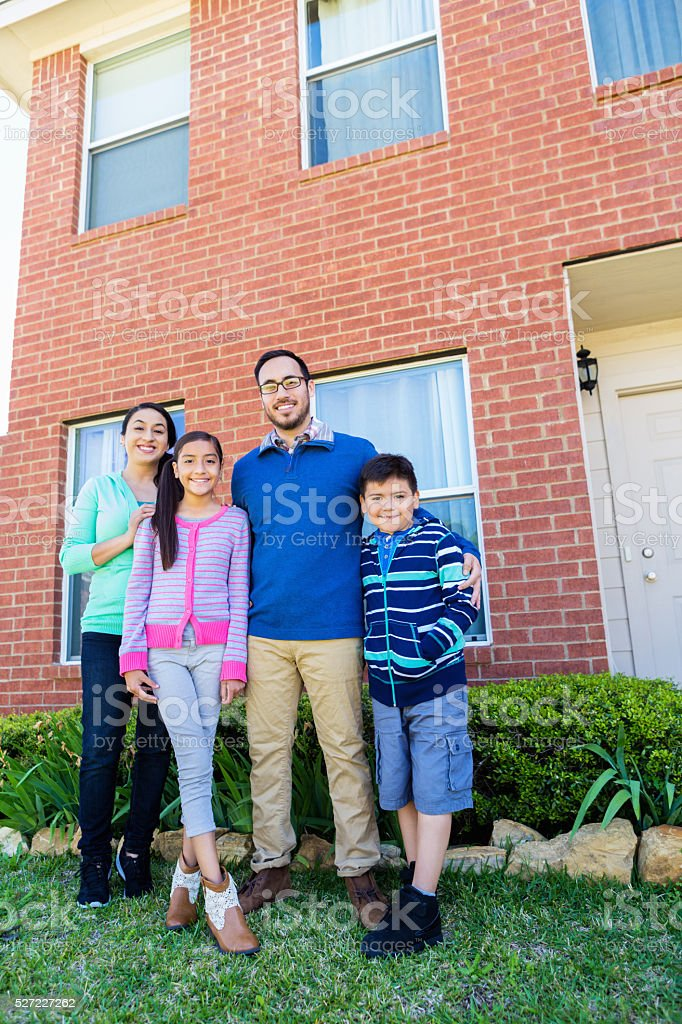 Excited family in front of their home stock photo