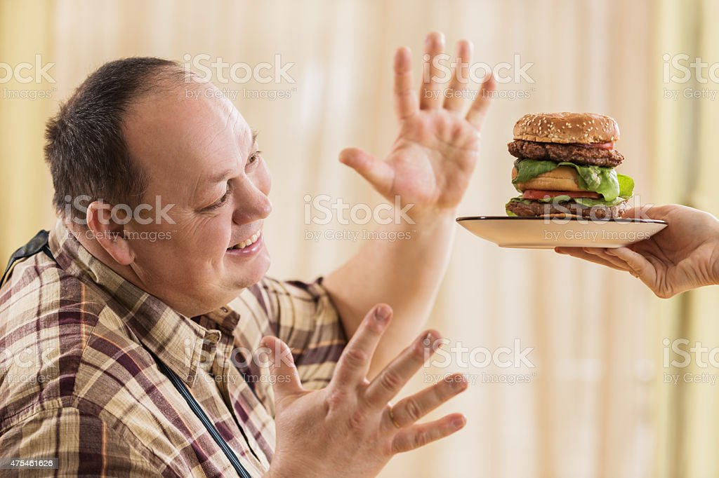 Excited fat man about to eat big hamburger. stock photo