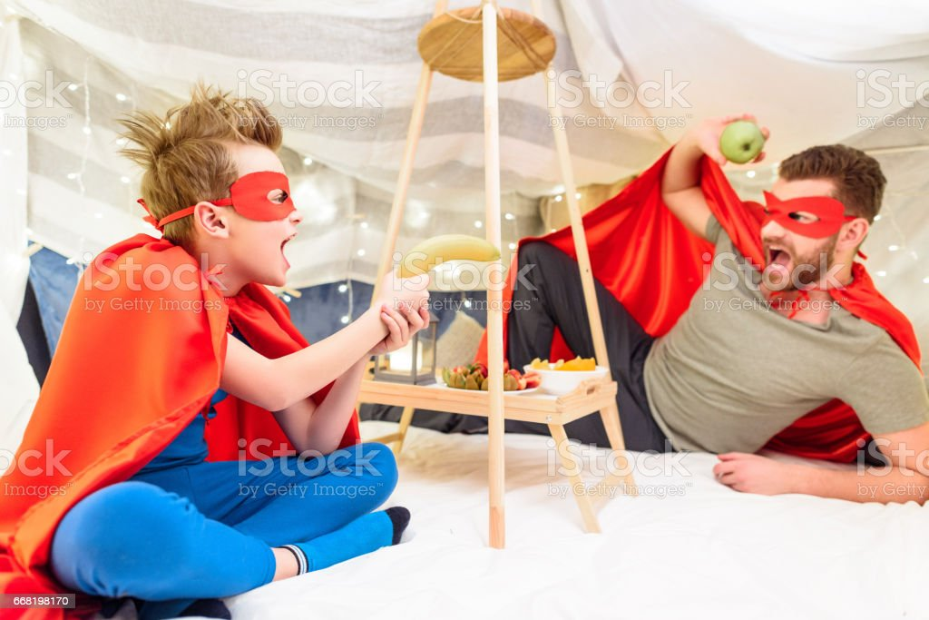 Excited father and son in superhero costumes having fun with fruits in blanket fort stock photo