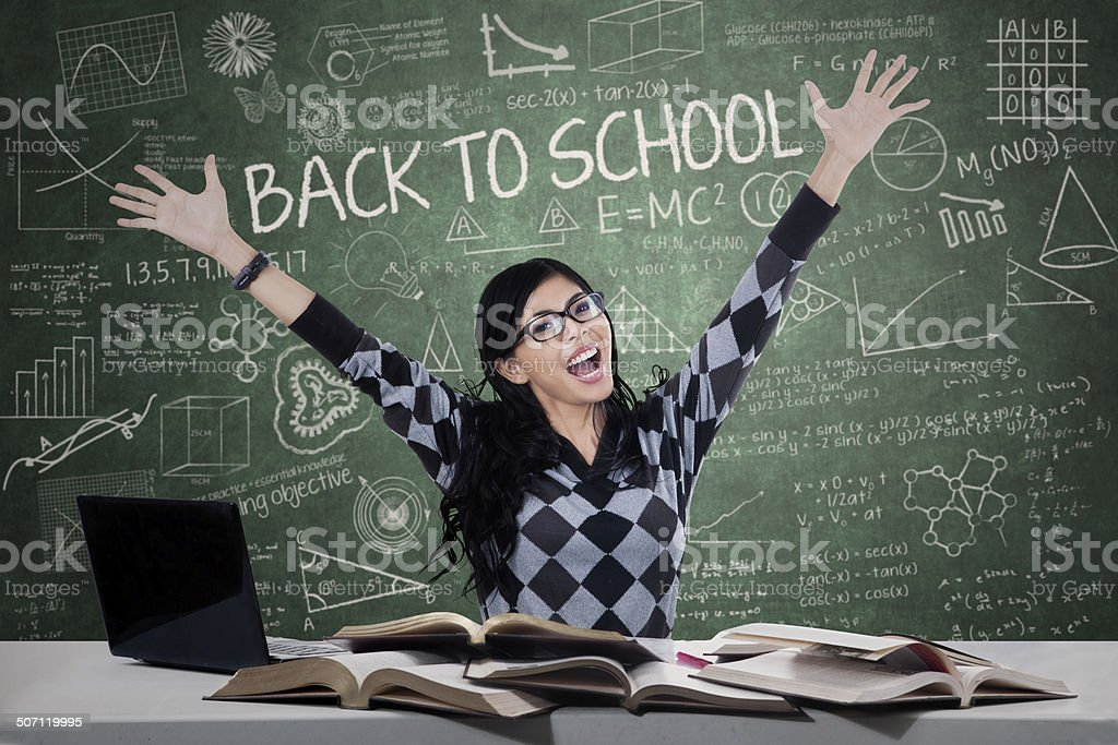 Excited female student in the classroom stock photo