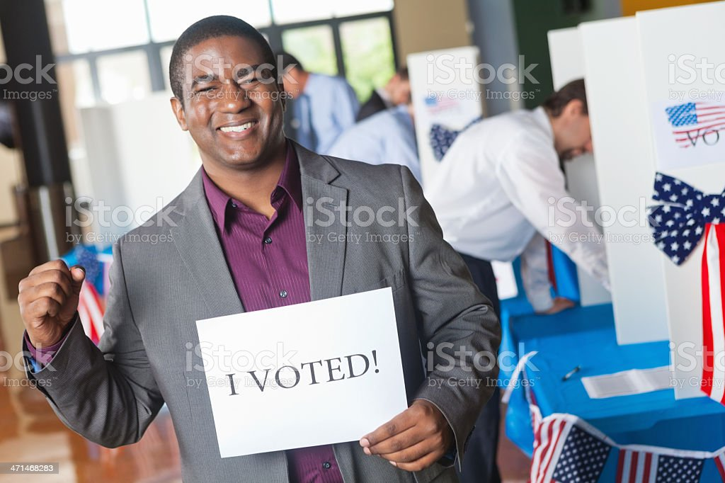 Excited first time voter at election center holding sign royalty-free stock photo