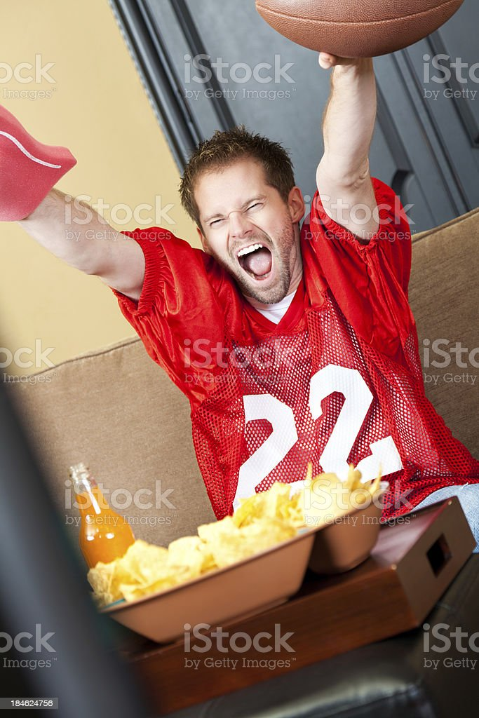 Excited football fan cheering for his team on TV royalty-free stock photo