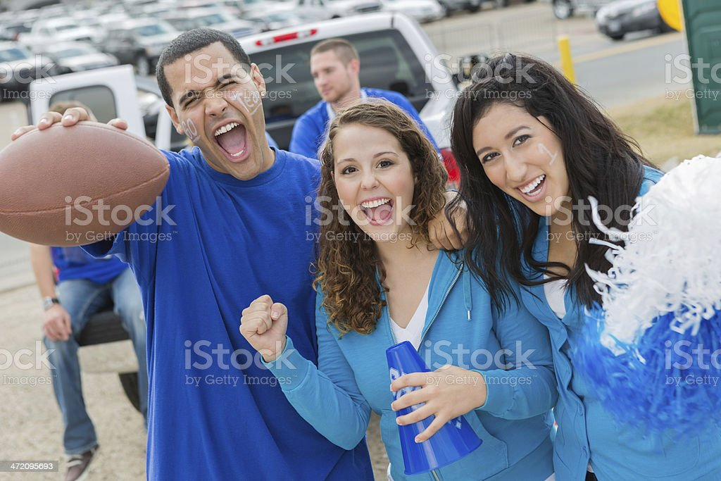 Excited football fans cheering for team at tailgate party stock photo