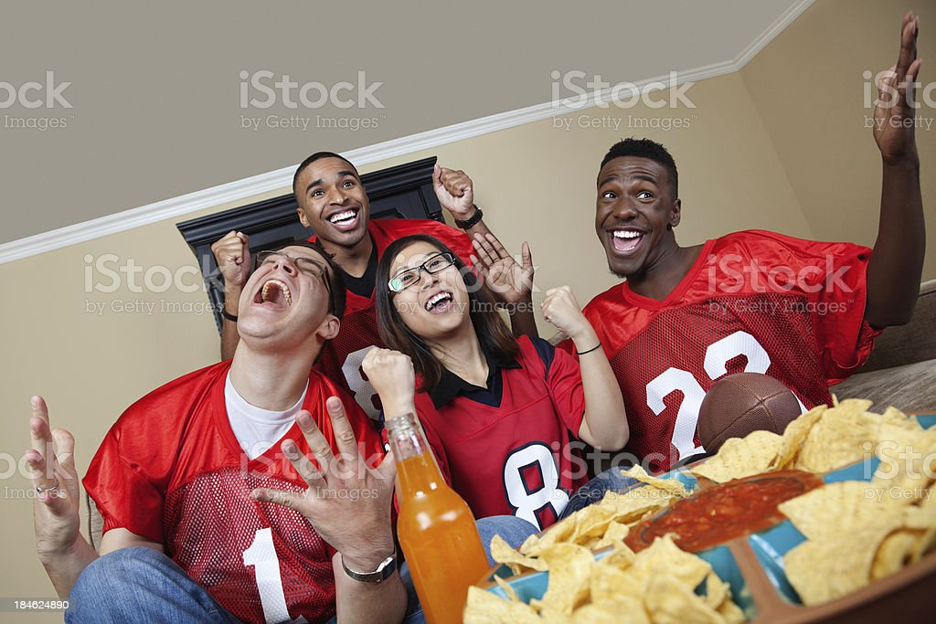 Excited football fans really into watching the game on TV stock photo