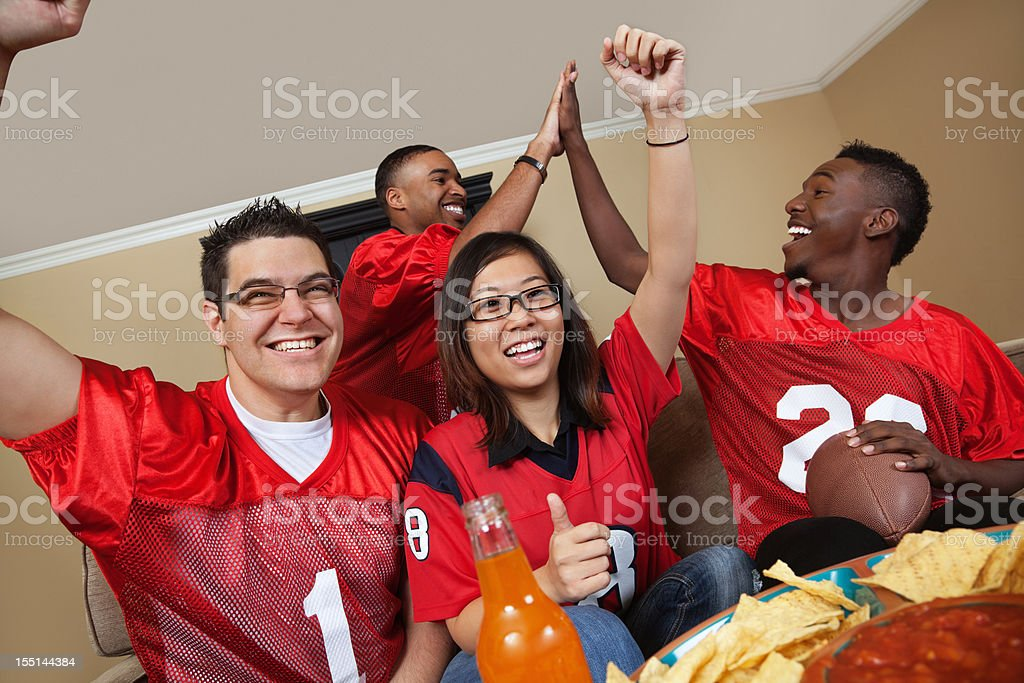 Excited football fans watching the game on TV together royalty-free stock photo