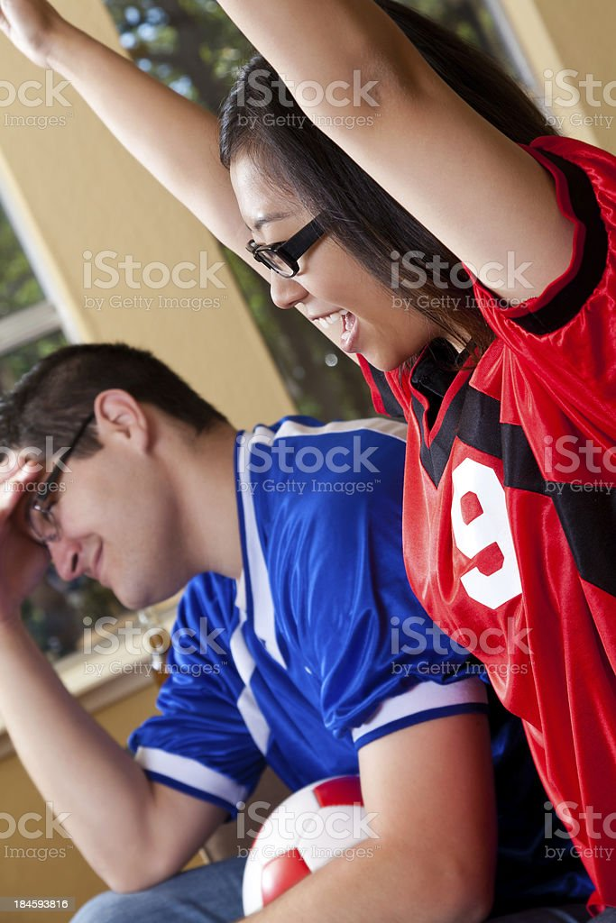 Excited friends cheering while watching soccer game on TV royalty-free stock photo