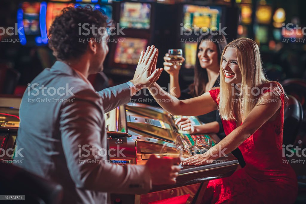 Excited friends   gambling at electronic roulette in casino stock photo
