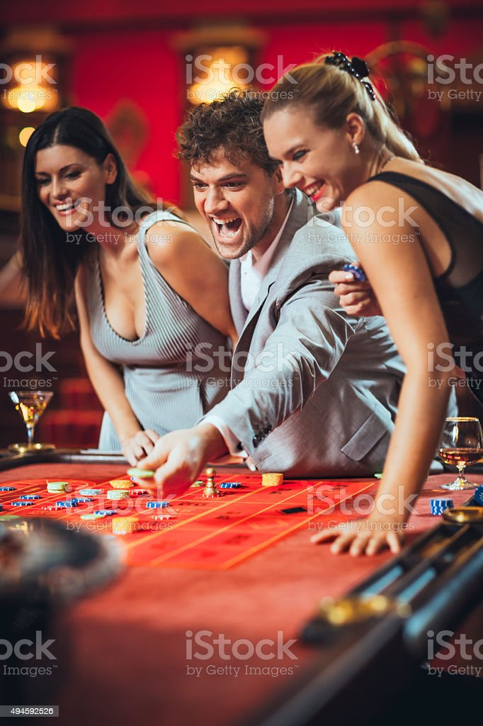 Excited friends   gambling at roulette in casino stock photo