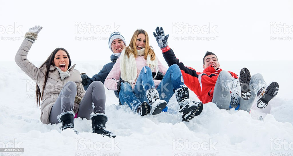 Excited friends having fun and sliding on snow. stock photo