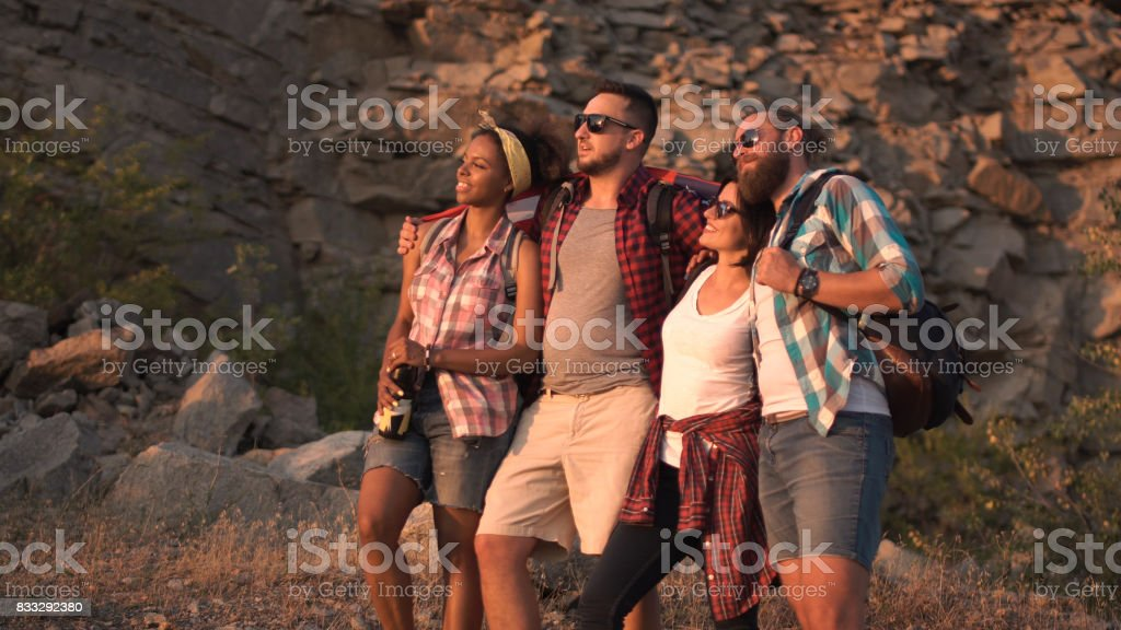 Excited friends posing among rocks with flag stock photo