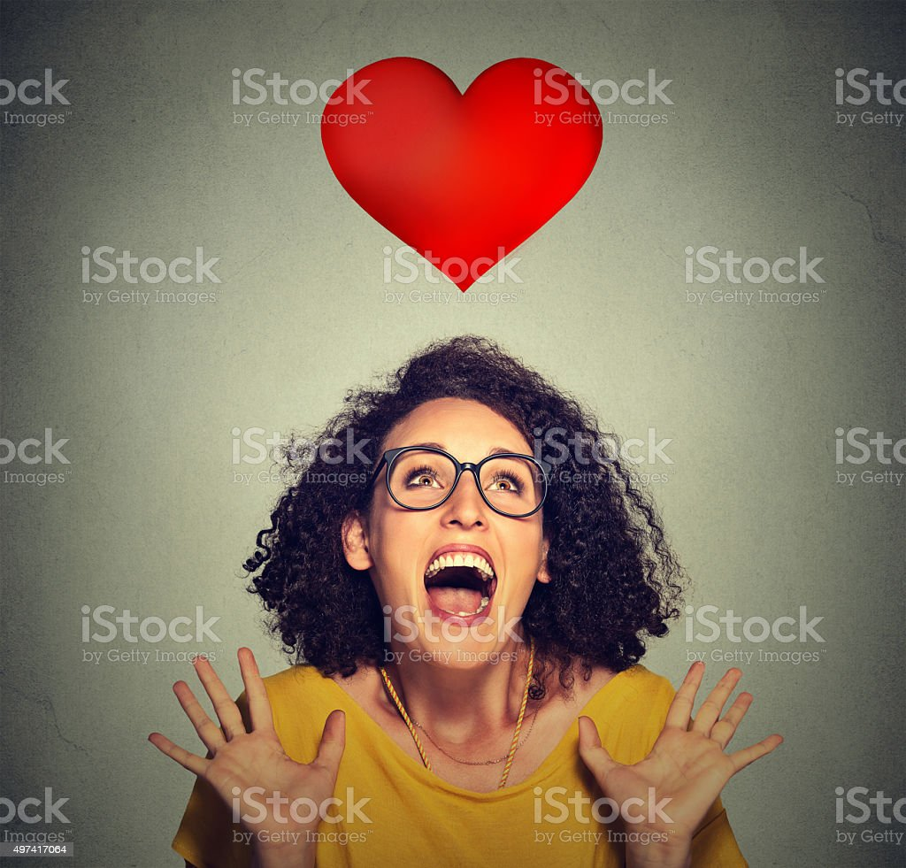 excited funky girl in love looking up at red heart stock photo