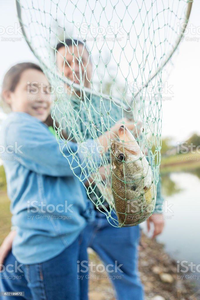 Excited girl catches fish with a net stock photo