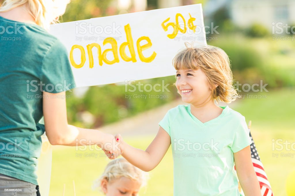 Excited girl getting business at her lemonade stand stock photo
