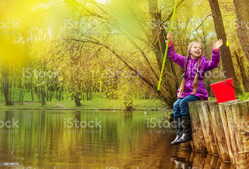 Excited girl holding fishrod out of the water stock photo