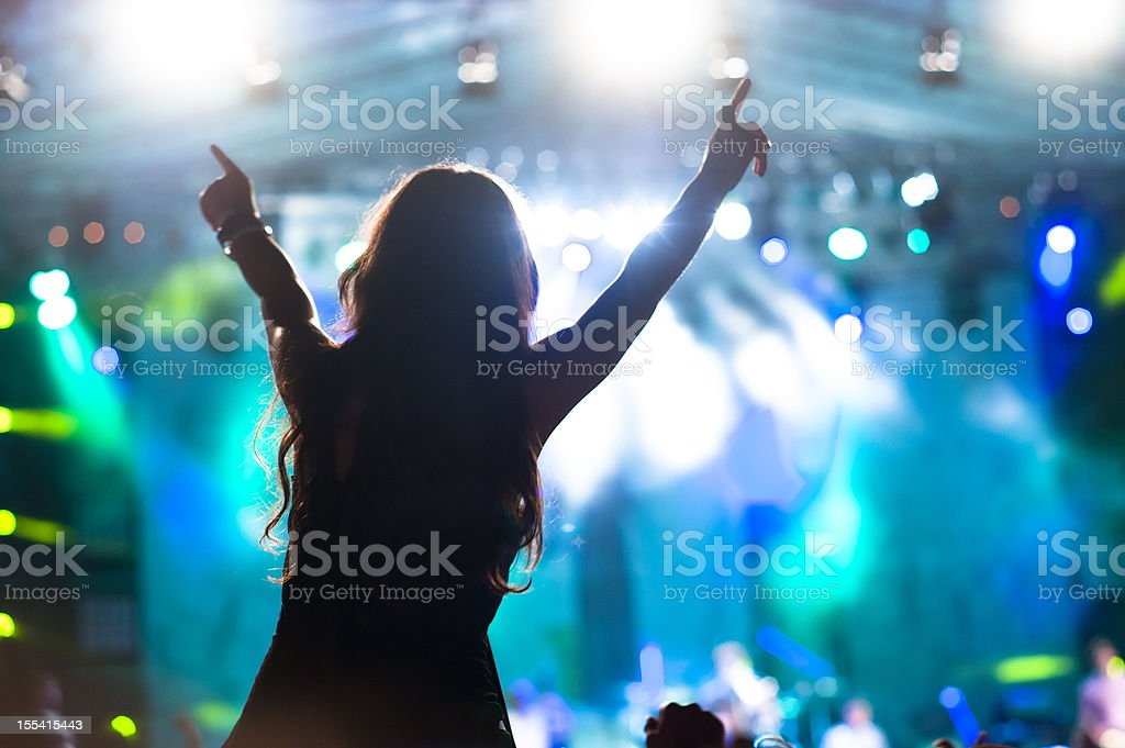 Excited girl stands at concert with blue stage stock photo
