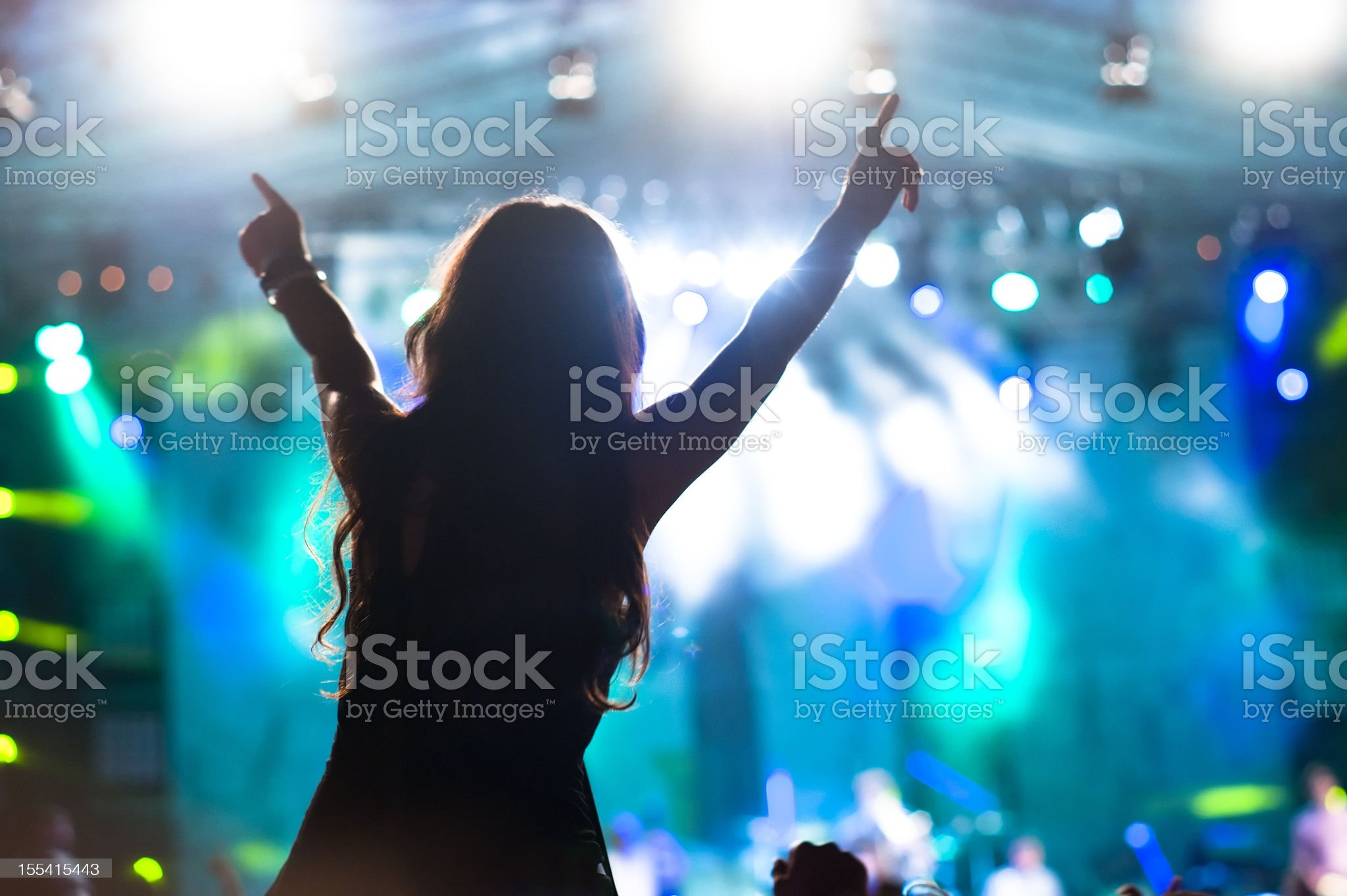 Excited girl stands at concert with blue stage royalty-free stock photo