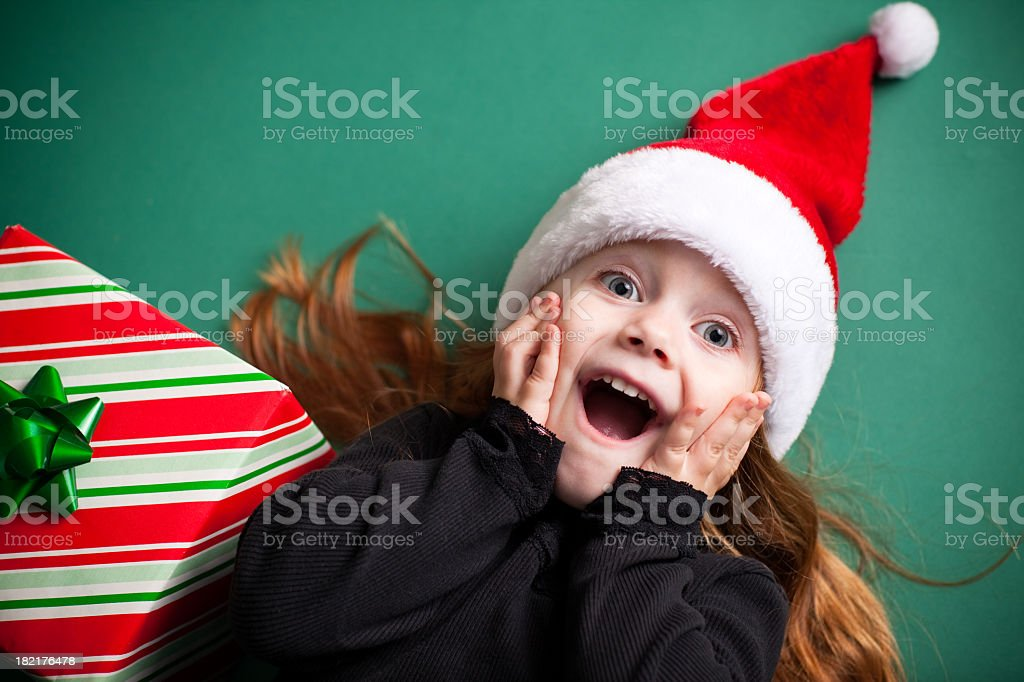 Excited Girl Wearing Santa Hat with Christmas Present royalty-free stock photo