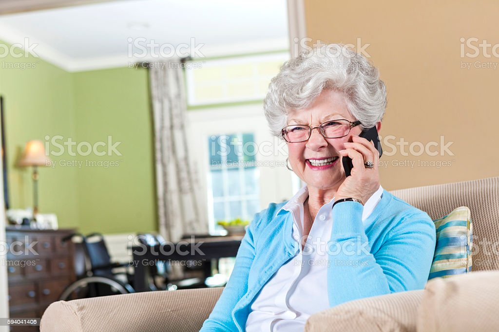 Excited grandma talks on smart phone in living room stock photo