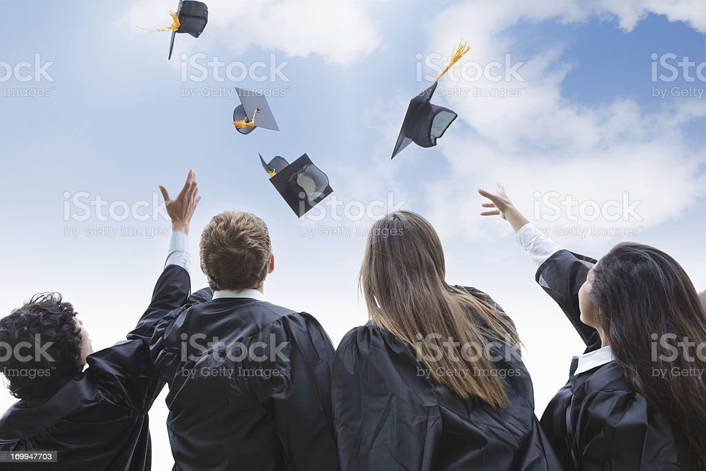 Excited group of college graduates throwing their hats in celebration stock photo