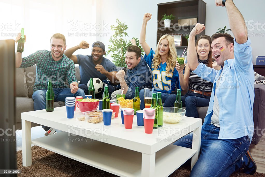 Excited group of friends watching sport on tv stock photo