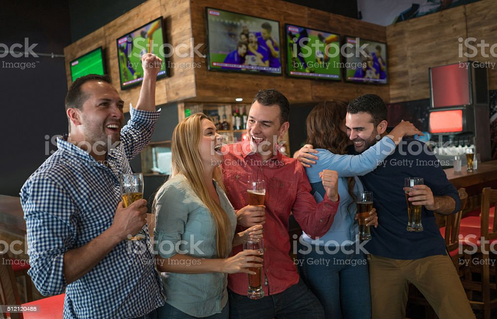 Excited group of people watching football at a bar stock photo
