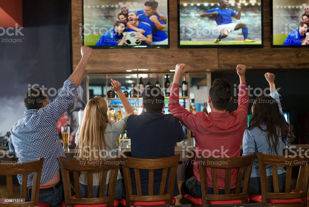 Excited group of people watching the game at a bar stock photo