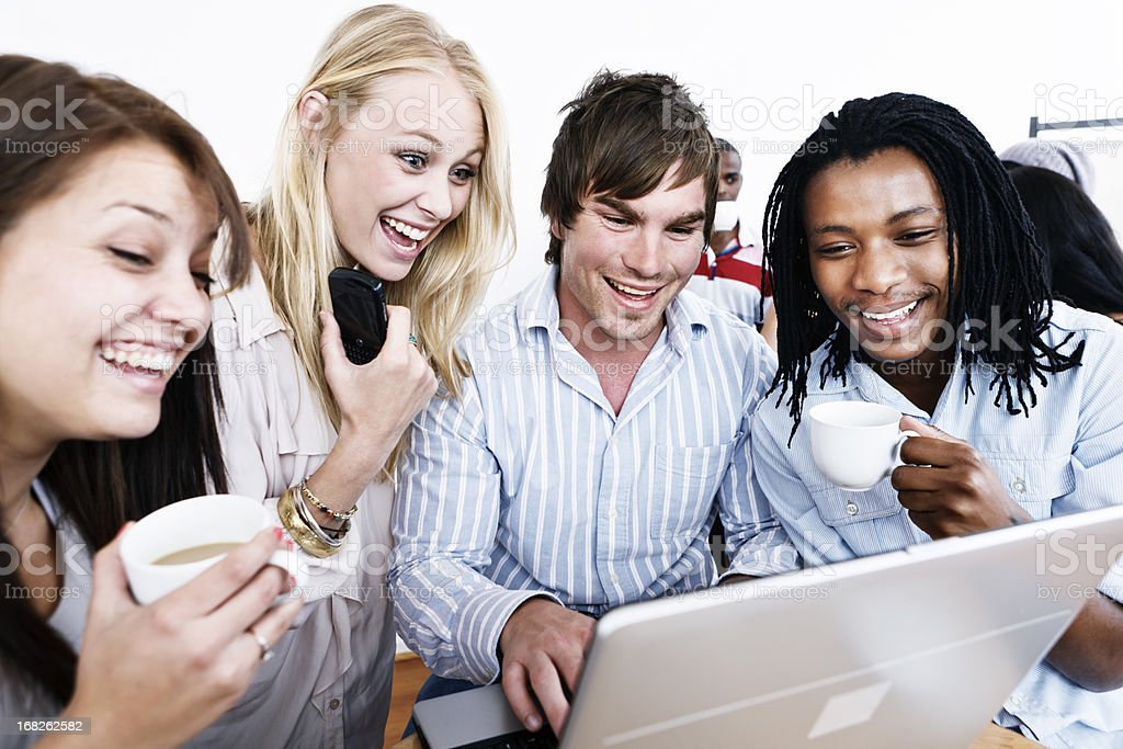 Excited group of young friends look at laptop screen royalty-free stock photo