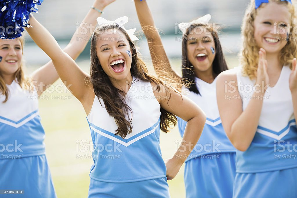 Excited high school cheerleaders performing at football game royalty-free stock photo