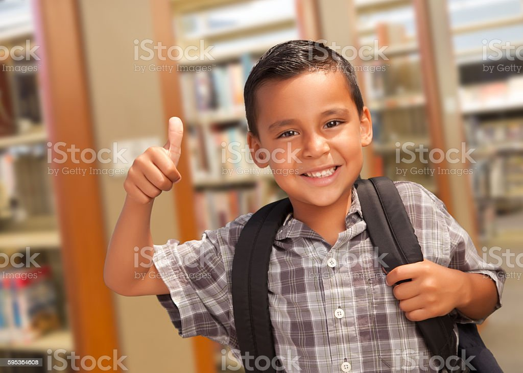 Excited Hispanic Student Boy Gives Thumbs Up in the Library stock photo