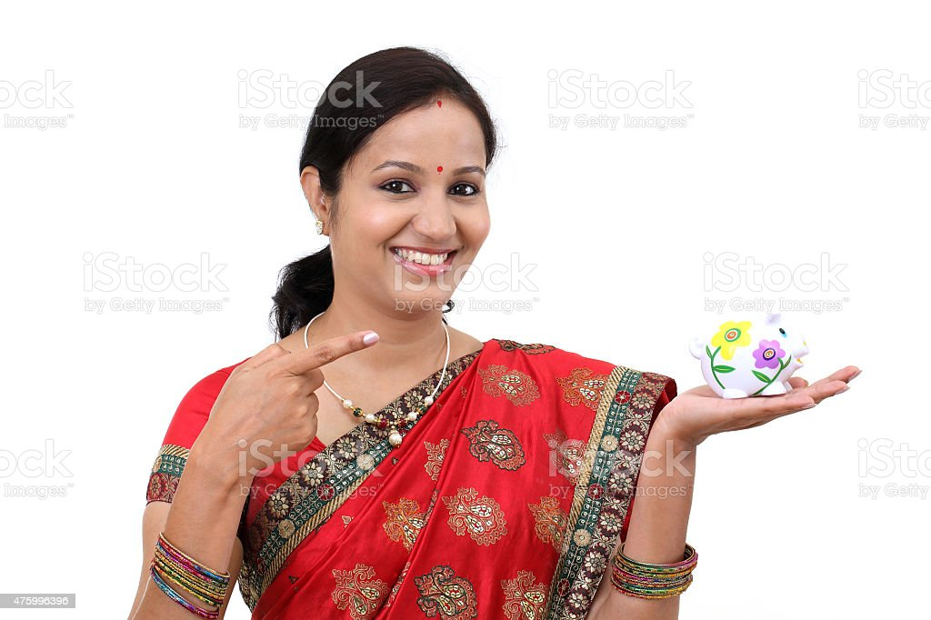 Excited Indian woman holding a piggy bank stock photo