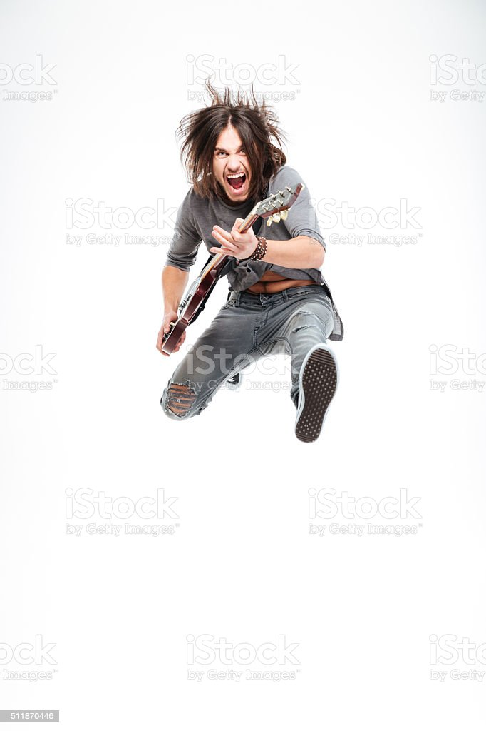 Excited joyful male guitarist with electric guitar shouting and jumping stock photo