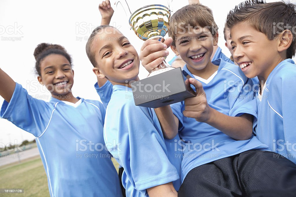 Excited kids' soccer team celebrating win with trophy stock photo