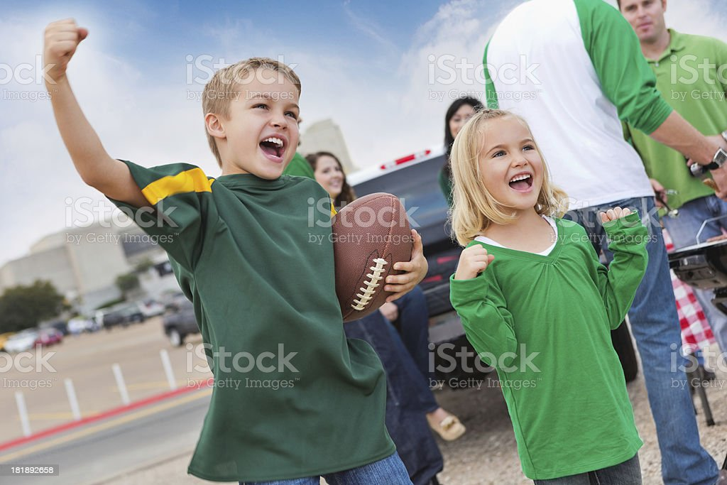 Excited kids tailgating with other fans at college football stadium stock photo