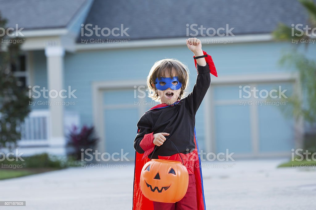 Excited little boy dressed in superhero costume for halloween stock photo