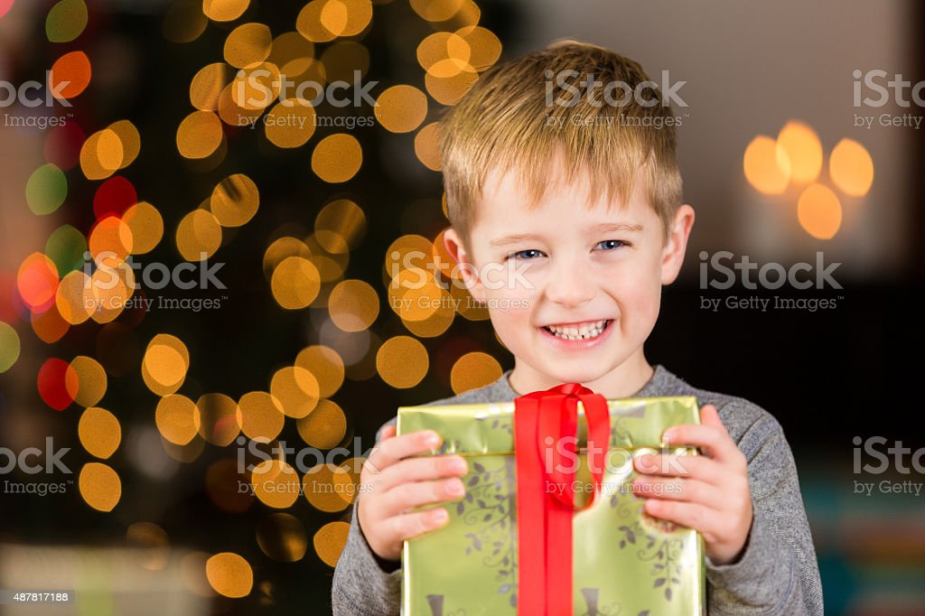 Excited little boy holding Christmas gift near tree stock photo