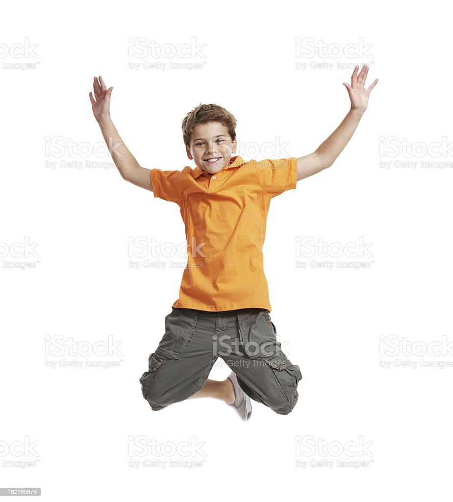 Excited, little boy jumping in mid air on white background stock photo
