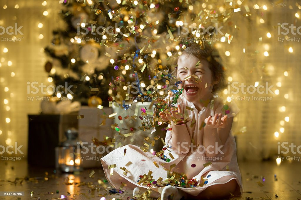 Excited little girl laughing, Catching confetti stock photo