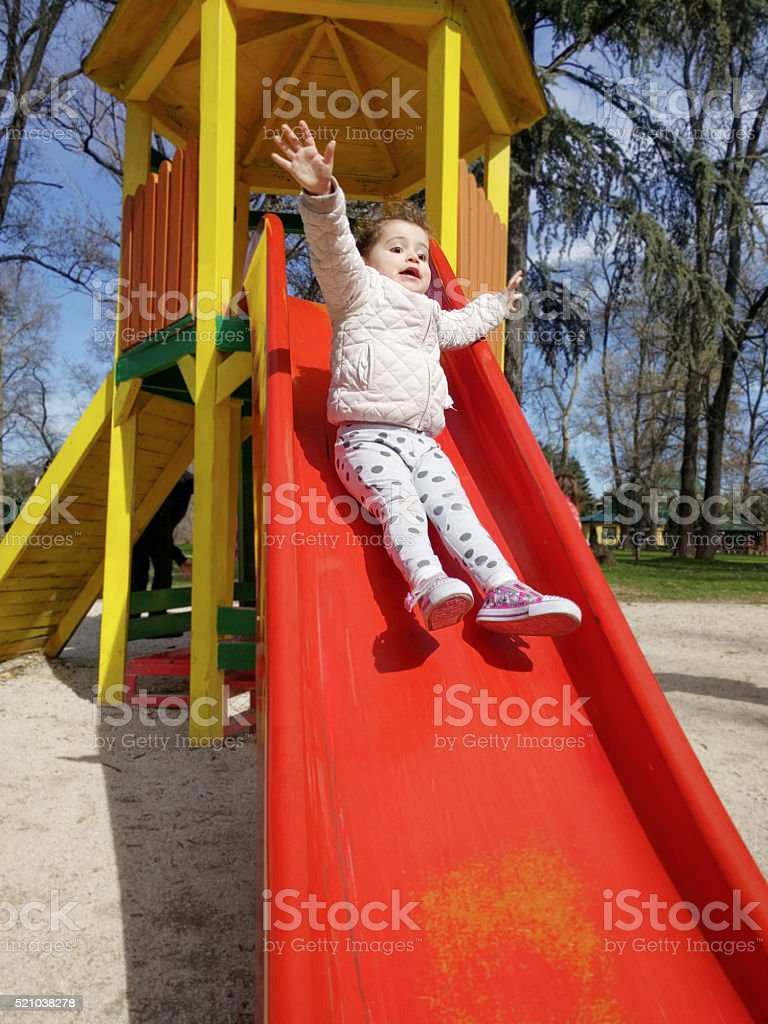 Excited little girl sliding down a slide stock photo