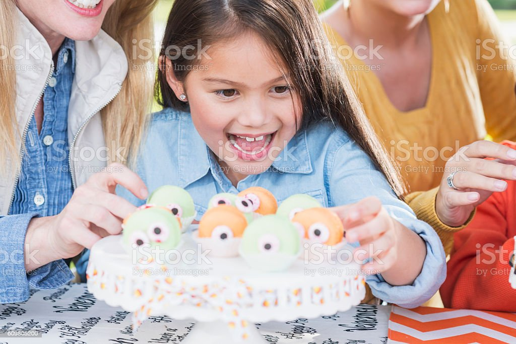 Excited little girl taking treat at Halloween party stock photo