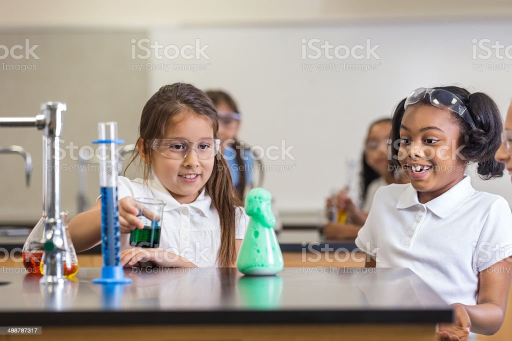Excited little girls learning chemistry in science class royalty-free stock photo
