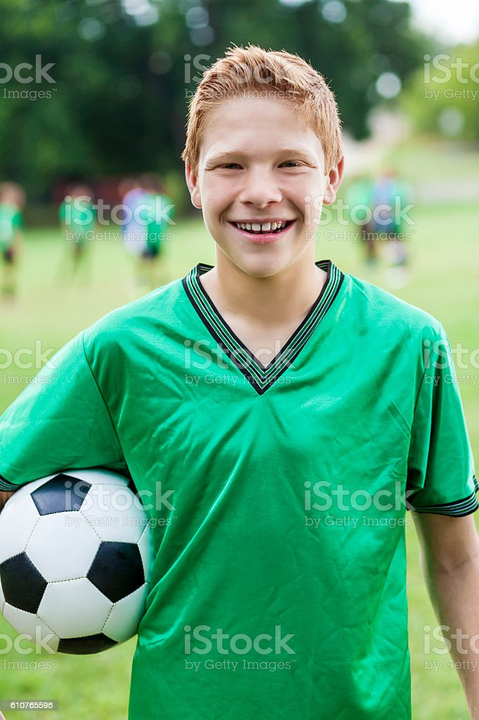 Excited male soccer player with ball stock photo